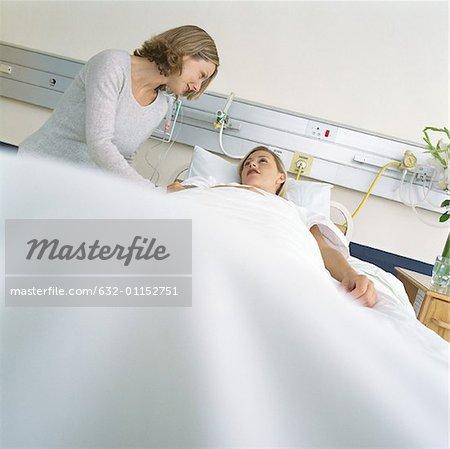 Besucher im Gespräch mit Patienten im Krankenhausbett
