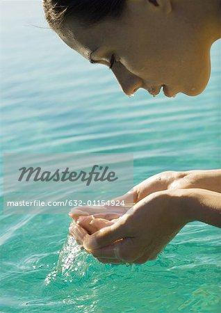 Femme visage penchée au-dessus de l'eau, l'eau dans les mains d'emboutissage