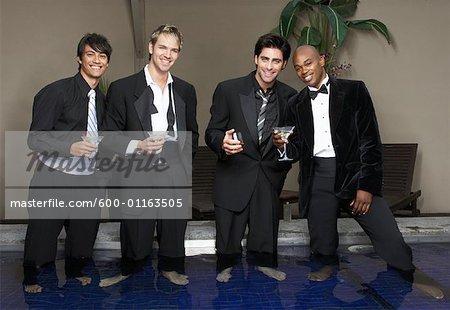 Men in Formal Wear debout dans la piscine, boire des Cocktails