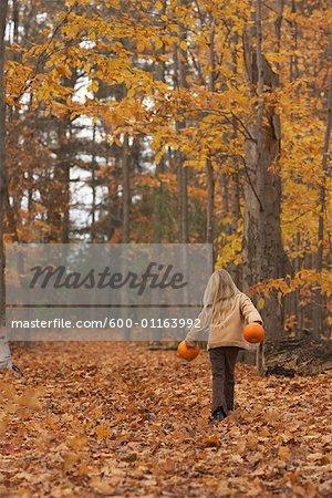 Mädchen zu Fuß durch Herbst Blätter