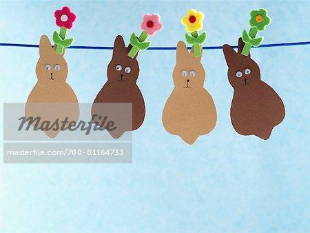 Lapins de Pâques papier suspendus sur la corde à linge