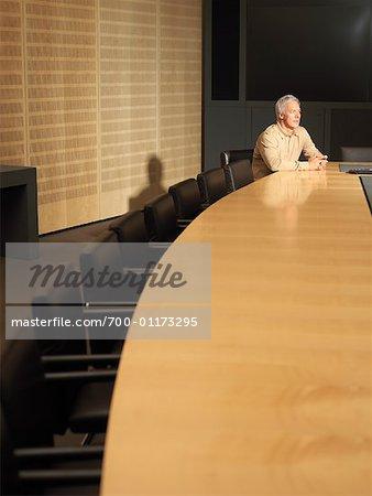Homme assis à la Table de la salle de conférence