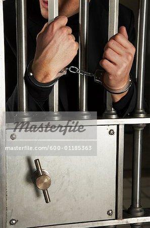 Homme menotté à la porte de coffre de banque