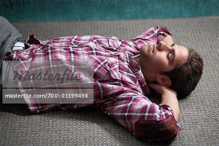 Homme couché sur le plancher