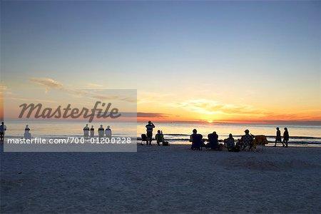 Gens sur la plage en regardant le coucher du soleil