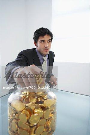 Businessman Grabbing Coins from Jar