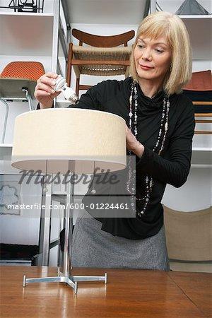 Woman Putting Lightbulb in Lamp in Furniture Store