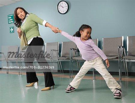 Mutter ziehen Tochter um den Doktor zu sehen