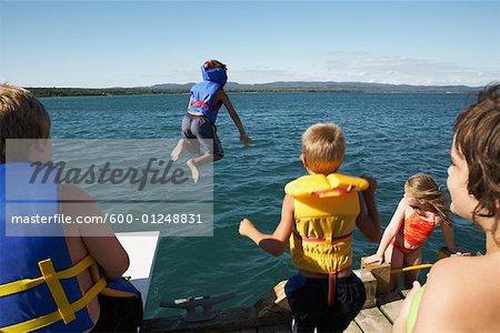 Kinder in Schwimmwesten Sprung in den See