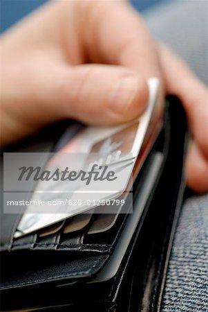 Gros plan de la main d'une personne en prenant une carte de crédit sur un portefeuille