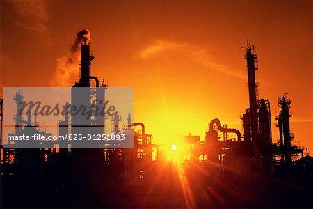 Usine de raffinage chimique et cheminées en silhouette