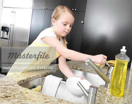 Kleine Mädchen waschen Gerichte
