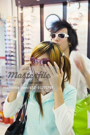 Couple d'adolescents essayer des lunettes de soleil boutique