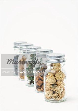 Bouteilles contenant des copeaux de bois, des herbes et des fleurs séchées