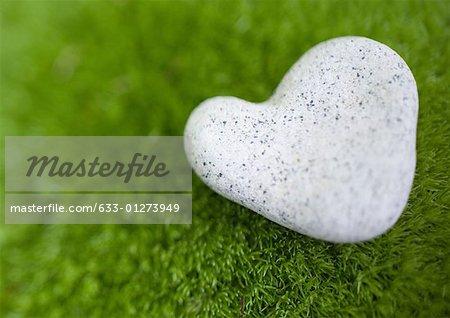 Coeur en forme de pierre sur la mousse