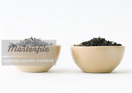 Feuilles de thé et lavande séchée dans des bols, côte à côte