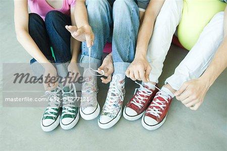 Amis assis sur le sol, à faible usure chaussures de toile, attacher les lacets, section