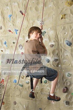 Garçon au gymnase d'escalade