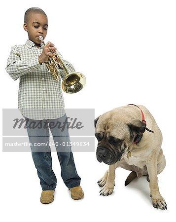 Boy blowing a trumpet near a dog