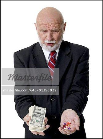 Gros plan d'un homme d'affaires détenant des pilules et des billets d'un dollar américain