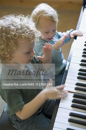 Vue d'angle élevé d'un frère et sa sœur jouant du piano