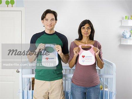 Portrait d'un couple debout devant un lit d'enfant et de la tenue des bavoirs