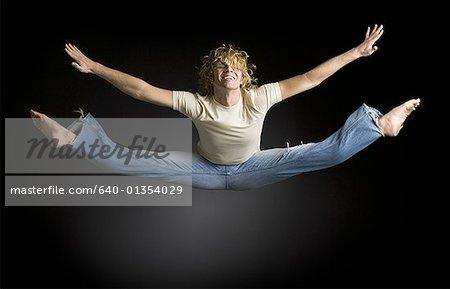 Jeune homme fait se divise dans les airs