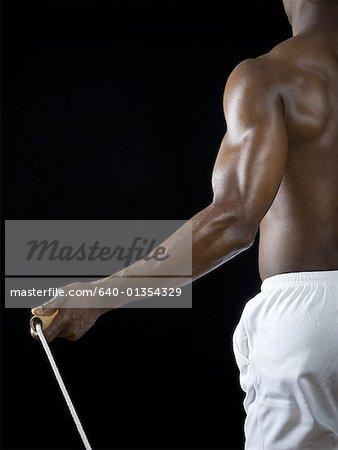 Milieu vue en coupe d'un jeune homme tenant une corde à sauter