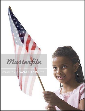 Gros plan d'une jeune fille tenant un drapeau américain