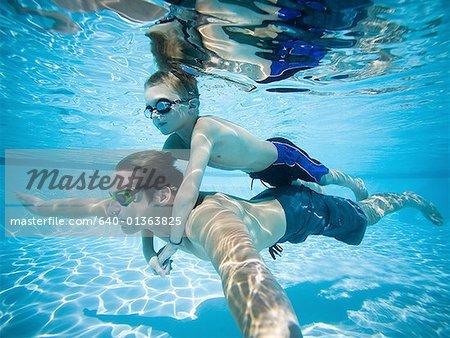 Père et fils, nager sous l'eau dans la piscine
