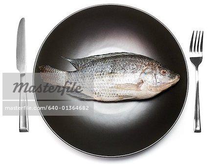Nahaufnahme von einem Fisch in der Pfanne mit einer Gabel und ein Messer