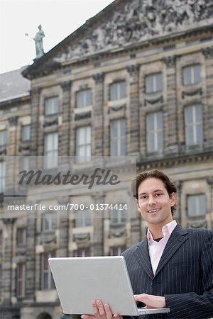 Homme d'affaires Holding Laptop, place du Dam, Amsterdam, Pays-Bas