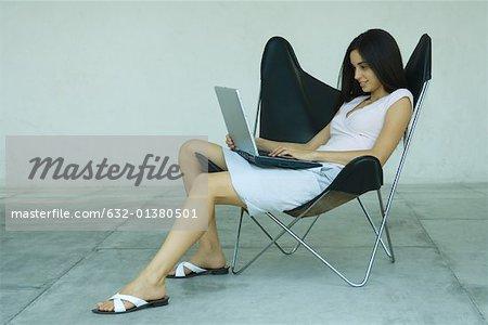 Frau im Sessel mit Laptop, in voller Länge