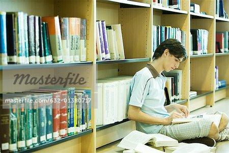Étudiant de niveau collégial masculin assis sur le plancher de la bibliothèque, étudiant