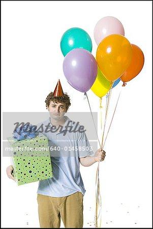 Mann mit Partyhut holding Ballons und Geschenk-Box schauen traurig