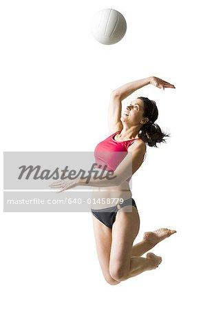 Woman in bikini jumping and playing volleyball