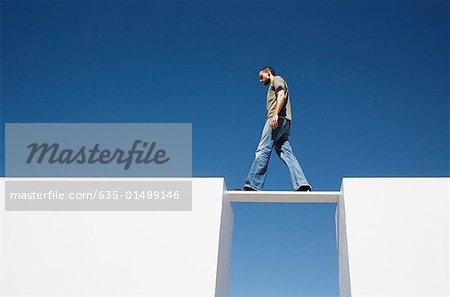 Man walking on board between two walls outdoors
