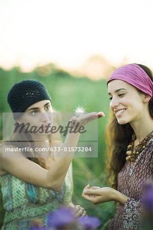À l'extérieur de deux jeunes femmes, l'un tenant la tige porte-graines de pissenlit sur la paume de la main