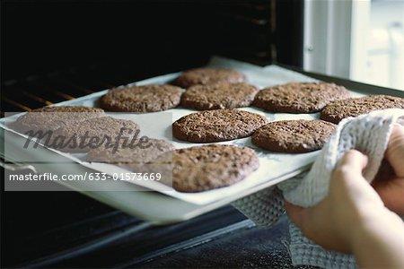 Blatt von Cookies aus dem Ofen nehmen