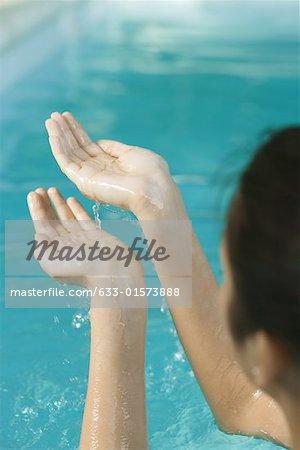 Jeune femme en levant les mains pleines d'eau, recadrée vue