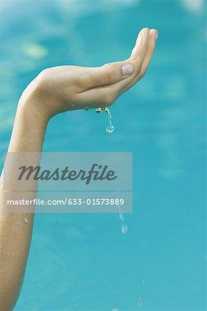 Jeune femme en levant la main en cuvette pleine d'eau, recadrée vue