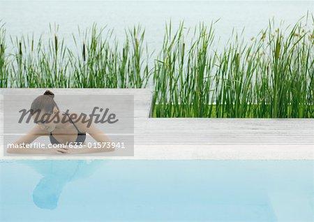 Jeune femme à côté de la piscine, en regardant le reflet dans l'eau