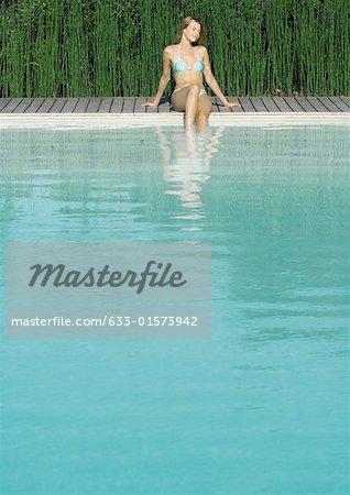 Jeune femme assise à côté de la piscine, balançant les pieds dans l'eau