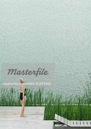 Femme en termes de maillot de bain sur le pont, regardant vers le plan d'eau