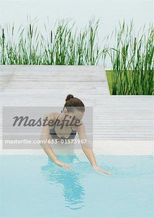 Jeune femme à côté de la piscine plongeant les mains dans l'eau