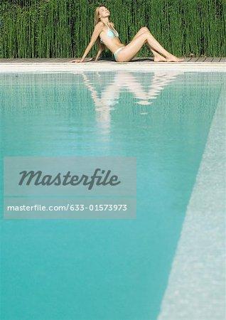 Jeune femme assise au bord de la piscine avec les genoux vers le haut, pleine longueur