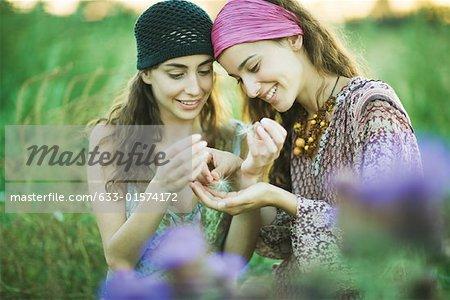 Femme jeune hippie regardant les graines de pissenlit