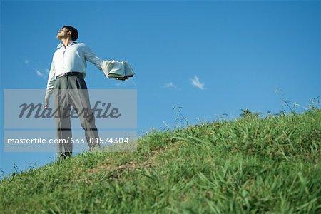 Homme debout sur la colline herbeuse, tenant livre, vue d'angle faible