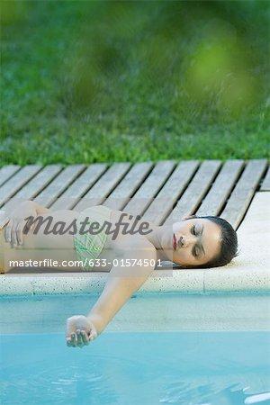 Jeune femme se trouvant en bord de piscine, maintenant l'eau en main en cuvette