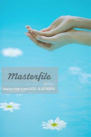 Jeune femme ventouses mains sur la surface de l'eau, flottant sous des marguerites